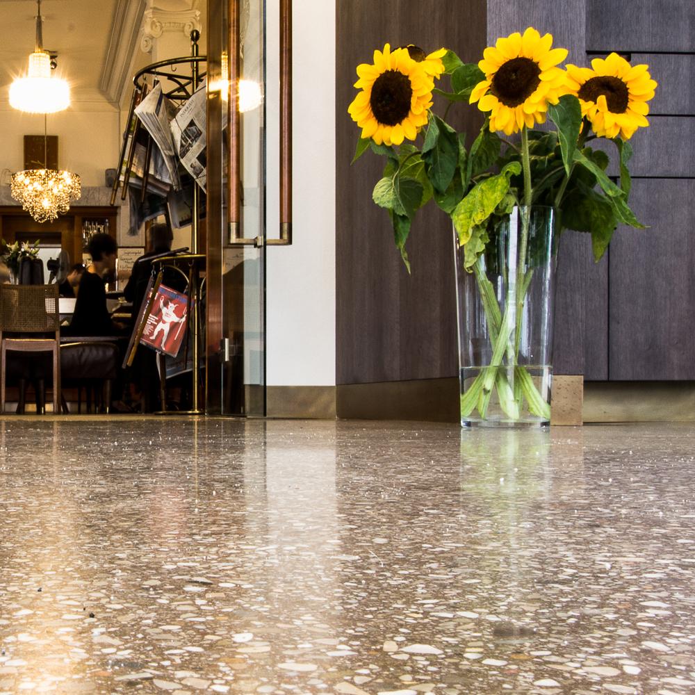 Terrazzoboden gänzend mit Sonnenblumen in Vase darauf